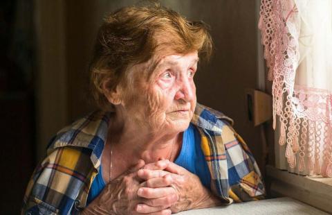 Una señora sentanda frente a una ventana, extrañando a su hijo.